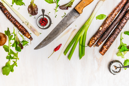 vegetables on white: Fresh vegetables and seasoning ingredients for healthy cooking with kitchen knife on white wooden background, top view, border