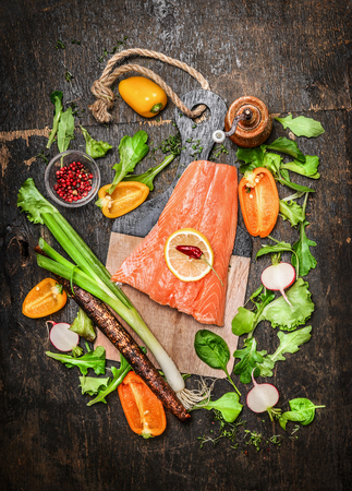 spinach salad: Salmon fillets fish on cutting board with fresh vegetables and spices ingredients on rustic wooden background, top view. Healthy clean food or diet cooking concept.