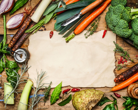 variety of vegetables ingredients for soup or broth cooking around blank sheet of paper on rustic wooden background, top view. Healthy clean food or diet concept.