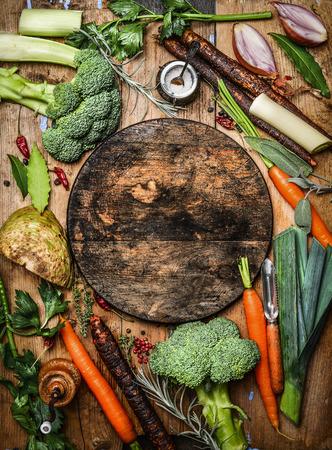 cooking: Frescos ingredientes org�nicos verduras para la sopa o caldo alrededor de la tabla de cortar en blanco r�stico redonda, vista desde arriba. La comida sana o concepto de cocina vegetariana.