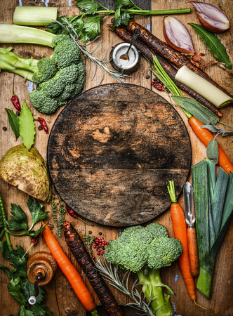 Fresh organic vegetables ingredients for soup or broth around round rustic blank cutting board, top view. Healthy food or vegetarian cooking concept.