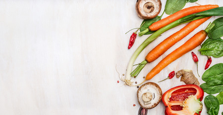 Fresh organic vegetables ingredients for tasty cooking on white wooden background, top view, place for text. Healthy  food  and diet concept.