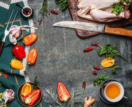 Ruwe gehele kip met olie en groente ingrediënten voor het koken op rustieke achtergrond, frame, bovenaanzicht. Gezonde voeding of dieet eten concept. Stockfoto