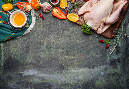 Raw whole chicken with oil and vegetables ingredients for tasty cooking on rustic background, top view, border.  Healthy food or diet eating concept.