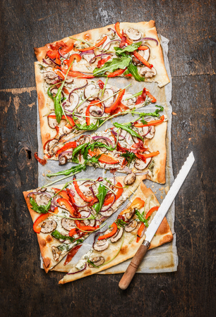 rustic kitchen: tarte flambe with Paparika, arugula and fresh cream with kitchen knife on rustic wooden background, top view