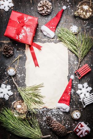 verticales: decoraciones de Navidad alrededor vaus hoja en blanco del papel, caja de regalo, sombrero de Santa y los copos de nieve en el fondo de madera rústica, vista desde arriba, marco, vertical
