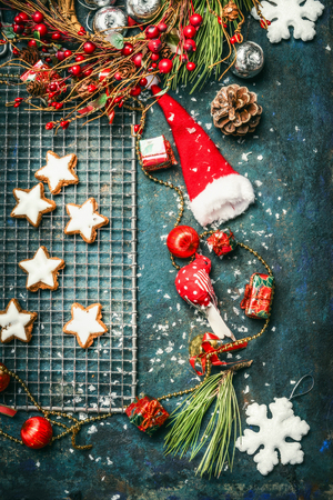 christmas cookie: Christmas cookie and winter decoration with Santa hat and wreath on rustic wooden background, top view Stock Photo