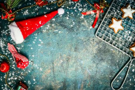 Kerst achtergrond met Santa hoed, sneeuw, rood winter decoratie en ster koekjes, bovenaanzicht, grens Stockfoto