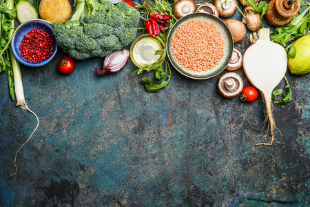 healthy grains: variety of vegetables, red lentil and ingredients for healthy cooking on rustic background, top view, horizontal border. Vegan food or diet eating concept.