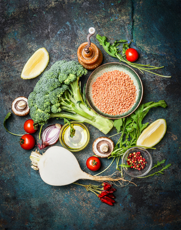 Fresh vegetables and ingredients with red lentil for healthy cooking on rustic background, top view, vertical border. Vegetarian food or diet eating concept.