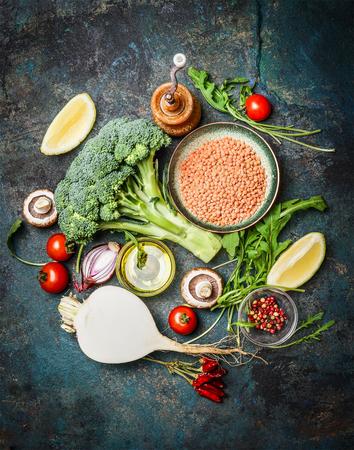 Verse groenten en ingrediënten met rode linzen voor gezond koken op rustieke achtergrond, bovenaanzicht, verticale grens. Vegetarisch voedsel of dieet eten concept.