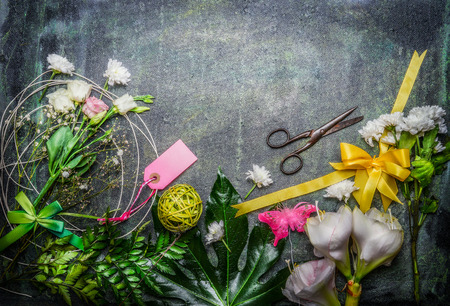arrangement: Beautiful fresh flowers, pair of scissors and tools to create bouquet on rustic background, top view, border.