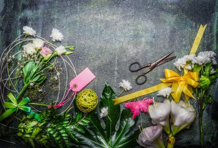 and bouquet: Bellissimi fiori freschi, paio di forbici e strumenti per creare bouquet su fondo rustico, vista dall'alto, di confine.