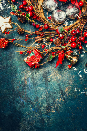 Vintage Christmas Hintergrund mit einem Kranz aus roten Winterbeeren, Feiertagsdekorationen und Plätzchen, Ansicht von oben, Grenze