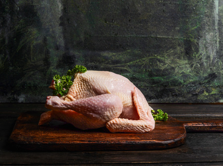black and white farm: raw whole chicken ready for cooking or roast on rustic kitchen table over dark background, side view. Stock Photo