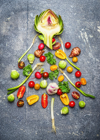 Christmas tree made of fresh vegetables on rustic gray background, top view.