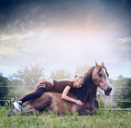 lies down: Woman lies and embraces a resting horse on nature background with sky