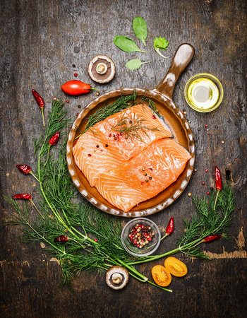 Salmon fillet in fried pan with herbs and ingredients for cooking on rustic wooden background, top view. Healthy food or diet nutrition concept Stock Photo