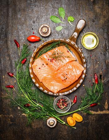 Zalmfilet in gebakken pan met kruiden en ingrediënten voor het koken op rustieke houten achtergrond, bovenaanzicht. Gezond voedsel of dieet voeding concept