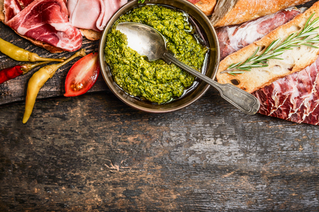 Green pesto and meat plate with bread and antipasti on rustic wooden background, top view, border. Italian food concept Stock Photo
