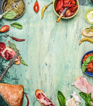 various antipasti with ciabatta bread, pesto and ham on rustic wooden background, top view, frame. Italian food and snack concept