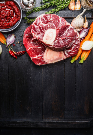 comida italiana: Veal shank slices meat and ingredients for Osso Buco cooking on dark wooden background,  top view, vertical border Foto de archivo