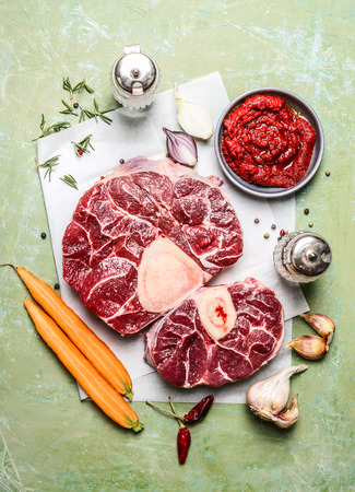 composing: Veal shank slices meat and ingredients for Osso Buco cooking, composing on rustic wooden background, top view