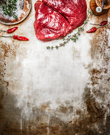 meat food: Raw steak with herbs and spices on rustic metal background, top view, place for text