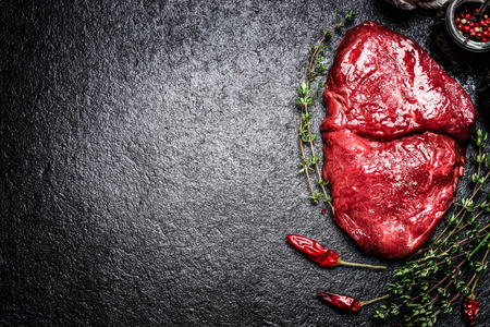 dark meat: meat beef steak with herbs and spices on dark background, top view, place for text