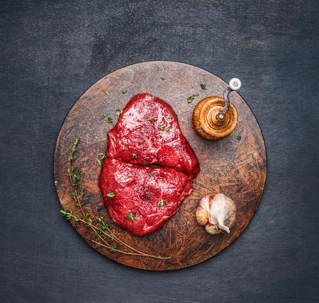carne cruda: filete de carne fresca con los ingredientes en tablero de corte redondo en el fondo de madera oscura, vista desde arriba Foto de archivo