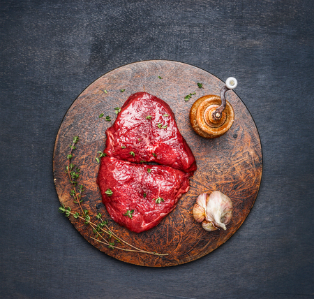 eating meat: Fresh meat steak with ingredients on round cutting board on dark wooden background, top view