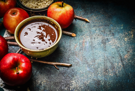 chocolate sprinkles: Hot chocolate in bowl and red apples  with twigs , ingredients for sweet apples making, preparation on rustic background, close up Stock Photo