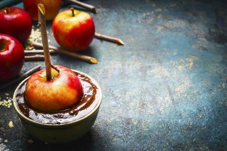 chocolatera: manzanas en cobertura de chocolate con los palillos en el fondo rústico