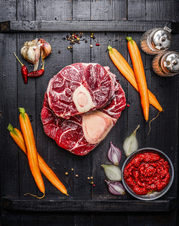 Raw veal shank slices meat and ingredients for Osso Buco cooking on black wooden background, top view Stock Photo