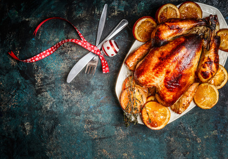 Roasted turkey or chicken with orange slices in plate for Christmas dinner served with fork,knife and festive decoration on dark rustic background, top view