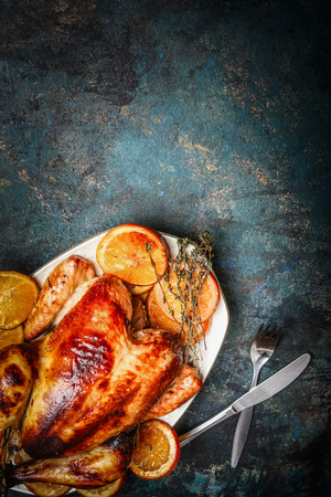 Roast chicken on platter and roasted orange slices served with fork and knife on rustic background, top view Standard-Bild