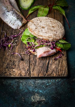 multi grain sandwich: Healthy fish sandwich with grain bread and fish on rustic cutting board