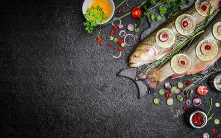 様々 な食材を用いた料理魚料理の食品背景。オイル、ハーブ、スパイス、まな板の上で生の char 平面図です。健康食品やダイエット栄養の概念。 写真素材
