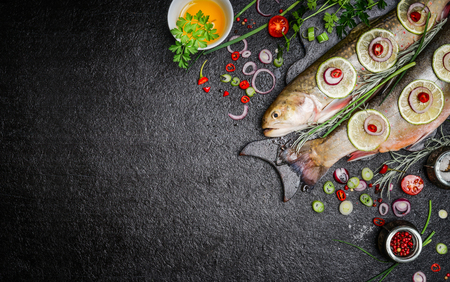 Food background for fish dishes cooking with various ingredients. Raw char with oil, herbs and spices on cutting board , top view.Healthy food or diet nutrition concept.