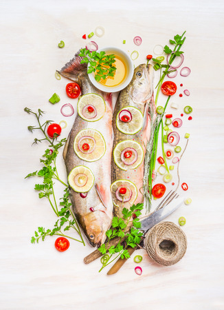 cocina saludable: Raw fish, colorful seasonning and delicious ingredients for Healthy cooking on white wooden background, top view Foto de archivo