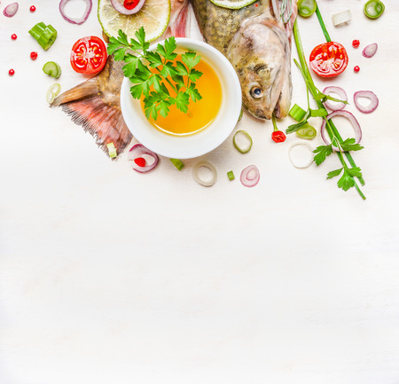 seasoning: Fresh tail and head of fish with oil and seasoning for cooking on white wooden background, top view. Healthy food or diet nutrition concept.