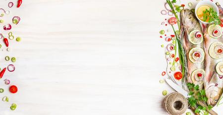 especias: Char pescado fresco con hierbas, especias e ingredientes para cocinar sabroso en el fondo de madera blanca, vista desde arriba, bandera. La comida sana o el concepto de nutrición de la dieta.
