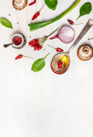 cuchara: Cuchara con aceite y especias y diversos ingredientes vegetarianos para una alimentación saludable en el fondo de madera blanca, vista desde arriba