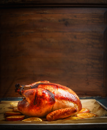 Tasty roasted turkey or chicken over wooden background, side view