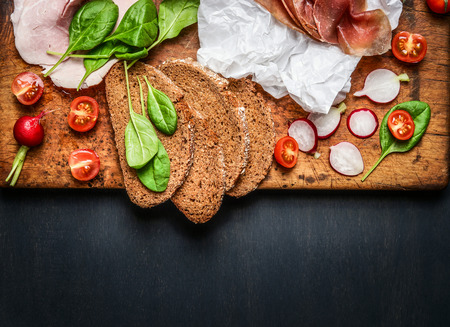dark meat: various ingredients for meat and ham sandwich  on dark wooden background, top view