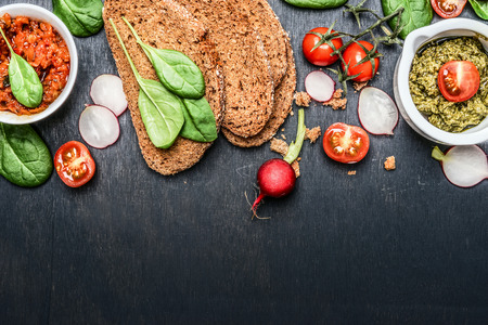 sandwich spread: Ingredients and spread for vegetarian sandwich making on dark wooden background, top view, border Stock Photo