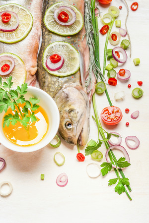char: Fresh whole fish with chopped ingredients for cooking, close up.   Char fish.Healthy food or diet concept