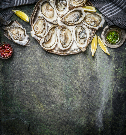 Opened oysters with lemon and various sauces  on rustic background, top view, place for text