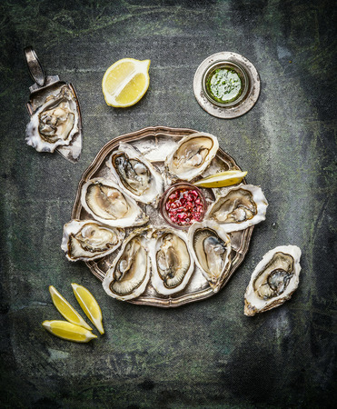 Oysters plate with lemon and various sauces  on rustic background, top view Foto de archivo