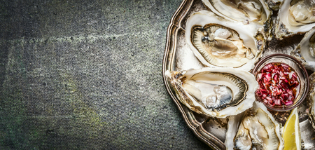 Oysters with lemon and shallots sauce on rustic background, top view, place for text, banner